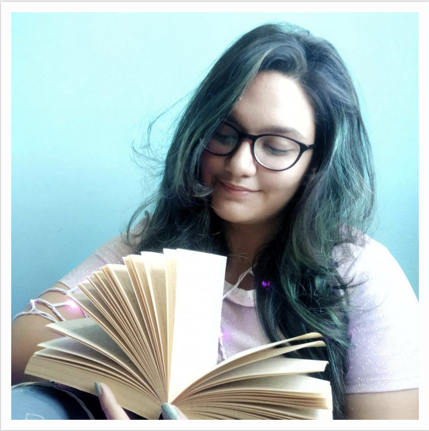 Charvi wearing glasses with eyes towards the open book in her hand. She has a slight smile.
